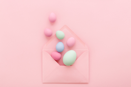 Easter Eggs in pink envelope on pink background. Happy Holiday message, correspondence concept. Flat lay, minimal style greeting card