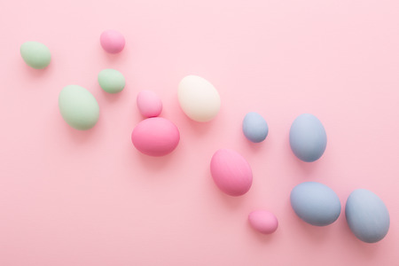 Spreaded colored Easter Eggs on pink  background. Happy Holiday greeting card. Flat lay, minimal style. Pastel colors