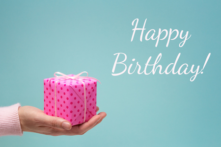Happy birthday greeting card with womans hand and pink dotted gift box. Stockfoto