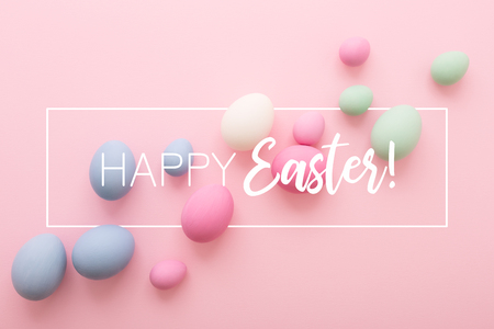 Easter greeting card with colored Eggs on pink background and inscription Happy Easter. Flat lay, minimal style, pastel colors.