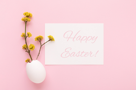 Minimal styled Happy easter holiday card decorated with eggshell and spring blooming branches. Top view. Stockfoto