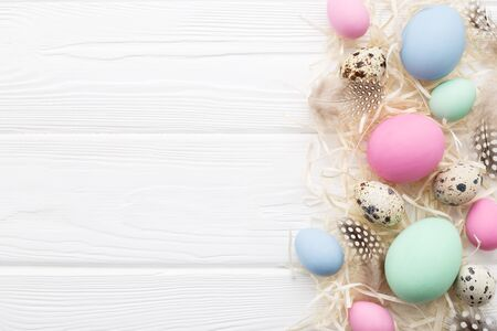 Easter eggs, straw and feathers on white rustic wooden table. Top view, copyspace. Holiday Frame in pastel colors