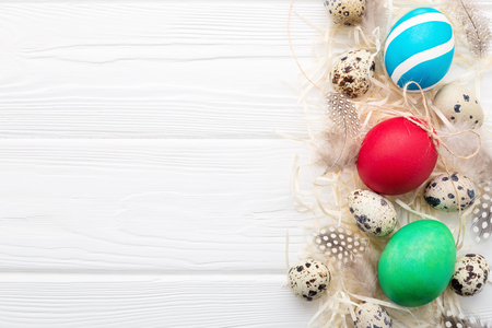 Painted Easter eggs, quail eggs, feathers & straw on white wooden background.  Border, Top view. Happy Holiday card Stockfoto