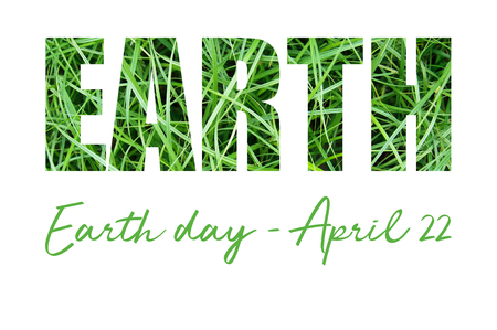 Concept card with Earth Day inscription on green grass. April 22.