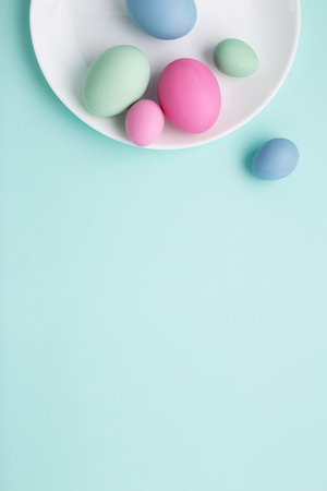 Conceptual Easter vertical background with white plate and painted eggs on turquoise surface. Top view, minimal. Stockfoto