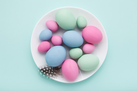 Group of colored Easter eggs on the white plate on turquoise background. Top view, holiday concept card.