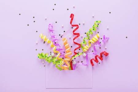 Confetti explosion. Festive streamers coming out of an opened envelope on violet background. Party Invitation concept. Flat lay, minimal style