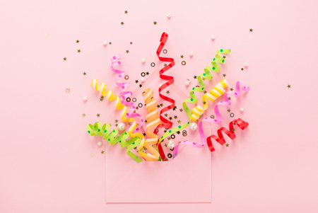 Confetti & sequins explosion. Opened envelope with festive streamers on pink background. Party Invitation concept. Flat lay, minimal style.