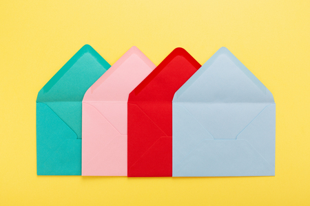 Abstract background with colorful envelopes on yellow paper. Conceptual card with association. Stockfoto