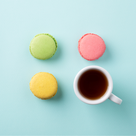 A square of a cup of tea with colorful macarons on light blue background. Minimal style, flat lay, top view. Stockfoto