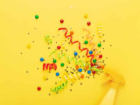 Party spray on yellow background. Bright creative background with explosion of serpentine, confetti and candies. Conceptual minimalism.