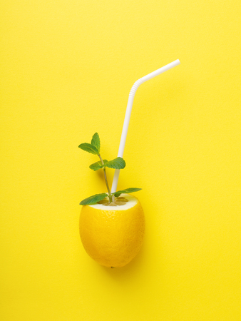 Lemon with white straw and mint on yellow background. Minimal styled creative summer concept. Imitation of a glass with lemonade. Stockfoto