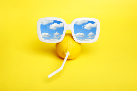 Mod yellow lemon with a straw in white sunglasses with cloudy sky reflection. Minimal  beauty & fashion summer vacation concept. Trendy bright colors.