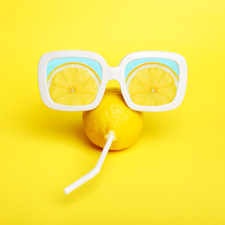Crazy lemon with a straw in white sunglasses with lemon slices reflection. Minimal  beauty & fashion summer mood concept. Trendy bright colors. Stockfoto