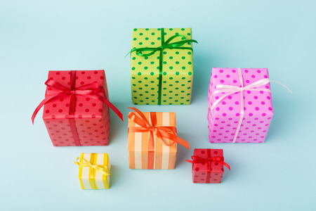 Different holiday colorful gift boxes wrapped in colorful paper and bows on blue background. Birthday, Christmas mood and sale concept. Stockfoto