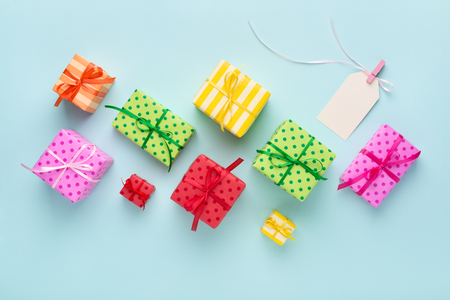 Holiday colorful gift boxes & blank gift tag tied with a ribbon on blue background. Birthday, Christmas sale concept. Stockfoto