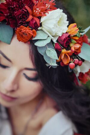 wreath of claret flowers on the head of a girl Stock Photo