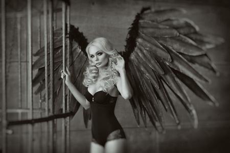 감 금 소에서 검은 날개를 가진 금발 여자입니다. 천사, 신비주의