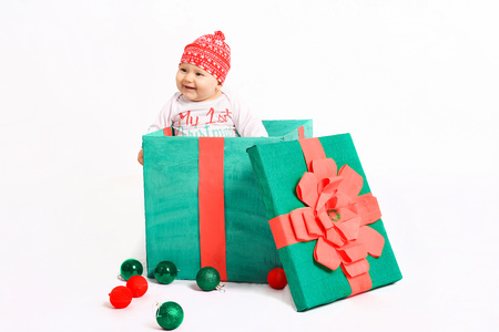 baby in a Christmas costume sits with gifts. beautiful New Years presents Stock Photo