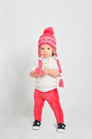 Little girl in a cap and sweater. Isolated on a gray background. Stock Photo