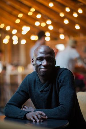 Handsome man sitting in a dark room. smile portrait