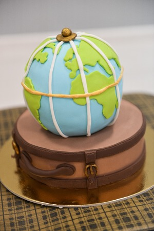 childrens themed birthday travel. smash the cake. sweet globe on a suitcase Stock Photo