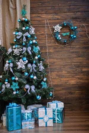 interior photo studio with Christmas decor. Piano, Christmas tree, gifts on a dark wood background Stock Photo