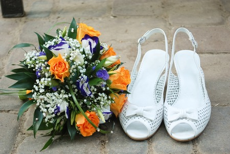 bridesmaid bridal shoes next to a bouquet of flowers Foto de archivo