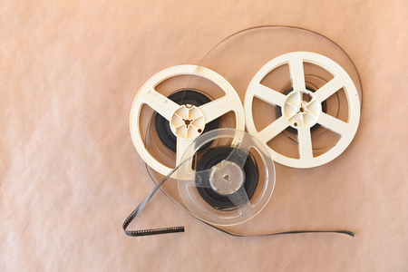 Old vintage cinematic reels with a video film lie on the background of the Kraft surface. Top view.