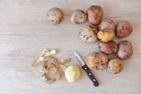 raw potatoes in the process of cleaning lies on a table next to a knife. cleaning, peel. clean potatoes Stock fotó