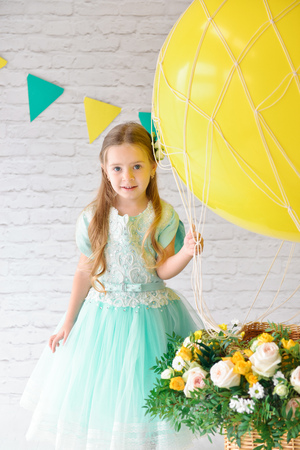 A girl in an elegant dress is standing in the studio next to a large balloon and a basket of flowers. Festive decor, birthday decorations