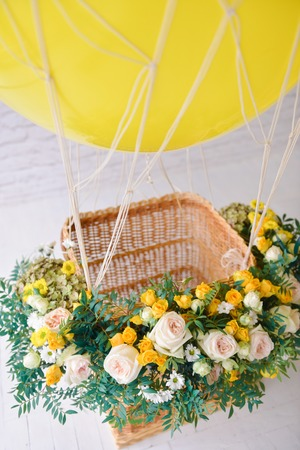 balloon with a basket decorated with live flowers, as a festive props for a childrens holiday birthday of yellow. close-up, details