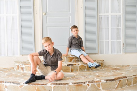 two brothers teenagers in an interior decorated studio on the background of the house