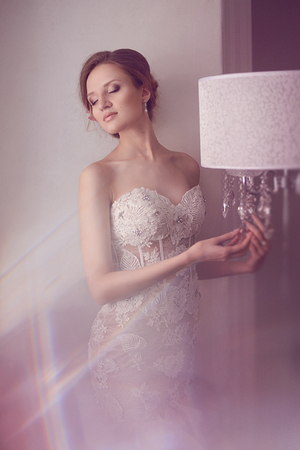 Tenderness Fashion Bride. Young beautiful model girl with perfect skin and makeup, in a wedding dress with rhinestones and lace, flowers in her hair. Soft focus, toning