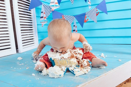 decoration for the boys birthday, smash the cake in a nautical marine style. stylized birthday ship photo shoot. Cheerful boy eats and break a cake with his hands on the first holiday
