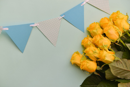 A bouquet of yellow roses flowers with leaves on an isolated blue background. Flat lay, top view. postcard birthday floral arrangement Stock Photo