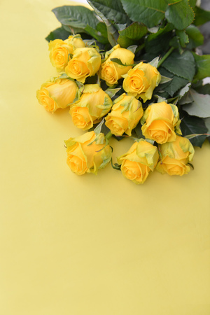 A bouquet of yellow roses flowers with leaves on an isolated background. Flat lay, top view. corner composition. postcard birthday floral arrangement