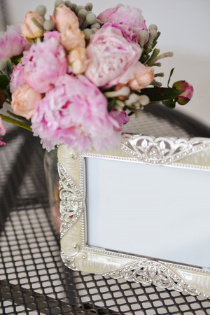 silver frame for a photo on the table next to a bouquet of pink flowers, soft focus