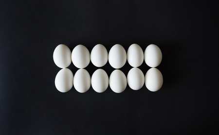 chicken eggs lie exactly in line, ordered on a black isolated background, top view 스톡 콘텐츠