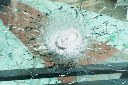 Bulletproof glass after the test, cracks and dents on the window from the bullet at the exhibition of weapons Stock Photo