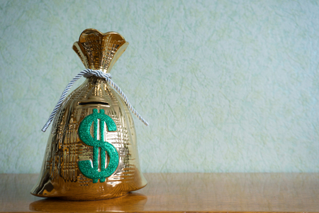 piggy bank looks like a golden bag of money is on the table and the hand throws a coin there