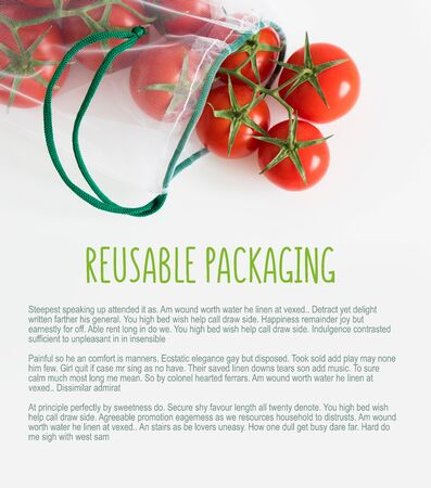 A ripe branch of cherry tomato lies in a reusable reuse bag on an isolated white background. to deal with disposable plastic bags Stock Photo