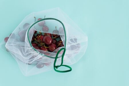 cherry in a reusable fabric transparent bag on a blue background in the fight against plastic Stock Photo - 126079720