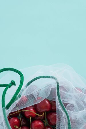 cherry in a reusable fabric transparent bag on blue background in the fight against plastic