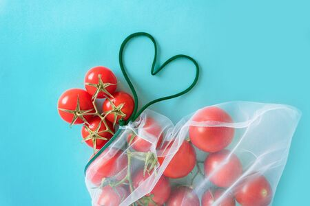A ripe branch of cherry tomato lies in reusable reuse bag on an isolated blue background. with love for the planet green heart of lace to deal with disposable plastic bags Stock Photo