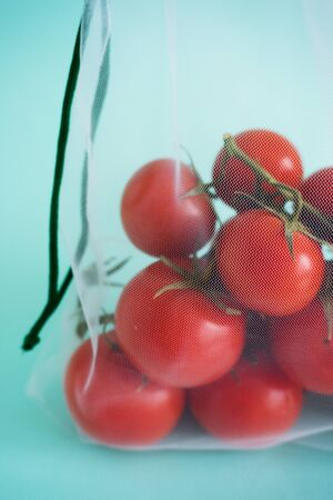 A ripe branch of cherry tomato lies in reusable reuse bag on an isolated blue background. to deal with disposable plastic bags