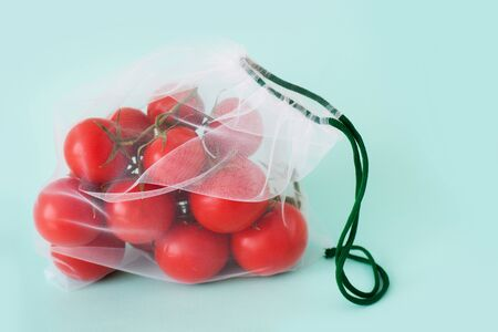 A ripe branch of cherry tomato lies in reusable reuse bag on an isolated blue background. to deal with disposable plastic bags Stock Photo - 126079762