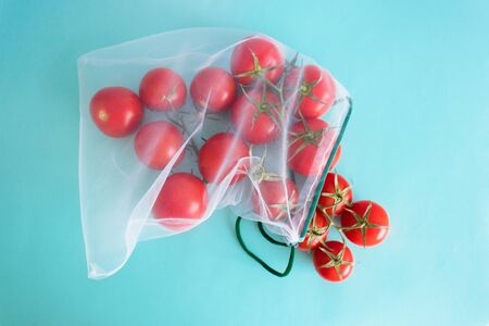 A ripe branch of cherry tomato lies in reusable reuse bag on an isolated blue background. to deal with disposable plastic bags Stock Photo - 126079763
