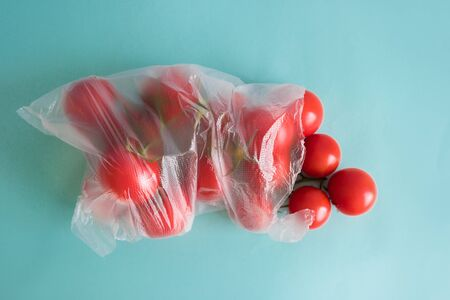 branch of ripe cherry tomatoes lies in a plastic bag on a blue contrasting background Stock Photo - 126079771