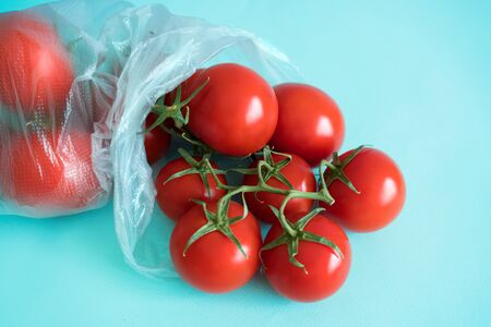 branch of ripe cherry tomatoes lies in a plastic bag on a blue contrasting background Stock Photo - 126079966